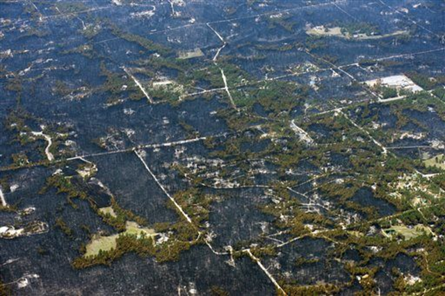 Aerial view of blackened areas that define the path of a wildfire that destroyed some homes and left others untouched in one neighborhood in the densely wooded Black Forest area northeast of Colorado Springs, Colorado, 13 June 2013. Photo: John Wark / AP Photo
