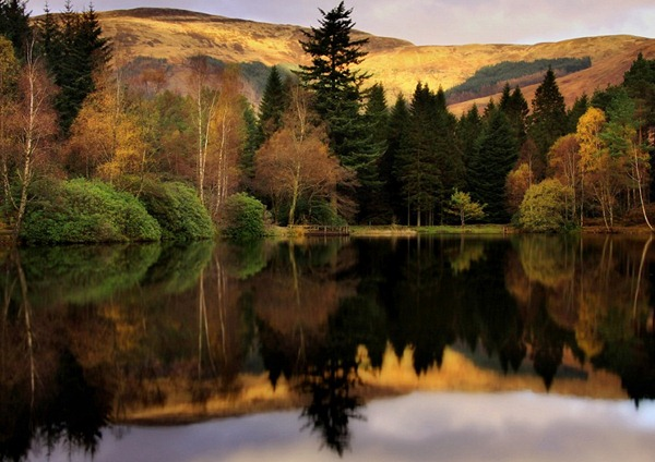 The hills of Glencoe are reflected in a loch, along with with the russets and greens of the trees by the water