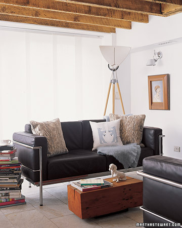 A black leather couch offsets the airy white walls of this cozy living room.