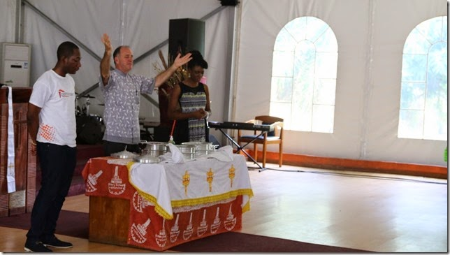 Steve at the communion table with Ebola Safe Elements