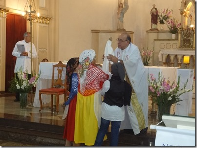 Pe. Ridz Antunes, Presidente da Celebração, recebe Nossa Senhora de Fátima dos Pastorinhos (representados pelas crianças)