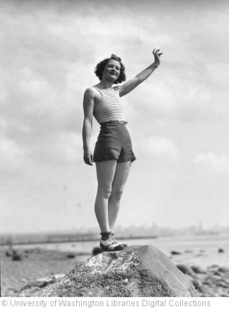 'Woman in a swimsuit waving while standing on a large rock on a beach, probably Washington State' photo (c) 1932, University of Washington Libraries Digital Collections - license: http://www.flickr.com/commons/usage/