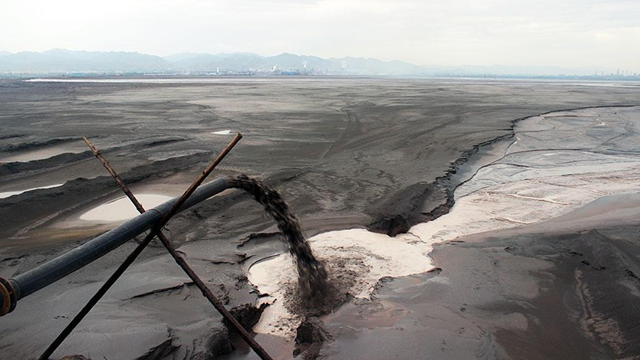 Hidden in an unknown corner of Inner Mongolia is a toxic, nightmarish lake created by our thirst for smartphones, consumer gadgets and green tech, discovers Tim Maughan. Black sludge pours into the lake - one of many pipes lining the shore. Photo: Liam Young / Unknown Fields