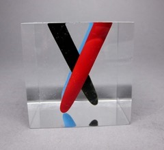 Acrylic cube pen holder or paperweight, in blue, black, and red