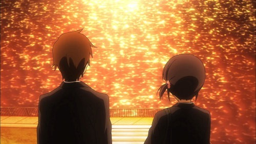 The backs of Taichi and Iori as they sit before a city river in the golden afternoon light