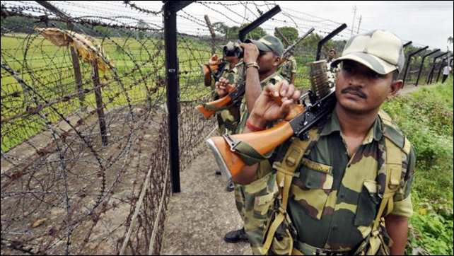 Indian Border Security Force personnel peer through the barb wire fence that separates India and Bangladesh during a security patrol in June 2013. By late 2013, about 1,700 of the fence's planned 2,116 miles had been built. When complete, nearly all of Bangladesh will be encircled by a militarized border. Photo: STRDEL / AFP  Getty Images
