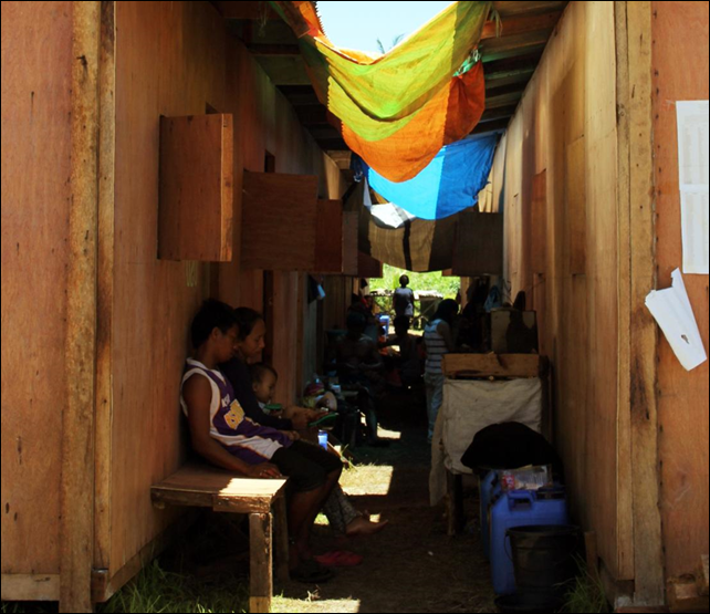 A family sits outside the bunkhouse where they continue to live after being displaced by typhoon Haiyan. Many of those in bunkhouses are being targeted for permanent resettlement to safer land as part of recovery plans. Photo: Genevive Estacaan / Oxfam 2014