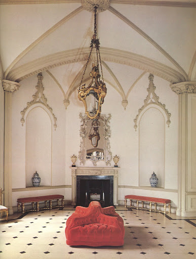 The gothic entrance hall of the Luttrellstown Castle, Dublin, includes a most interesting French tufted red velvet chair simply set in the center of the room.