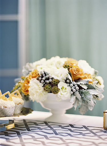 Arrangements of cream-colored flowers (hydrangea, ranunculus, pieris) dotted with gray dusty miller foliage, silver brunia, and muted peach garden roses were used.