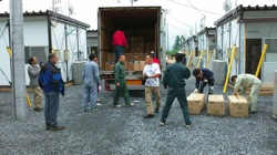 Volunteers bringing supplies into the temporary housing