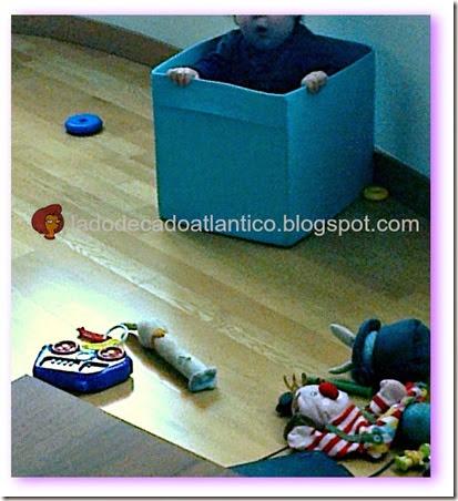Foto do Miguel escondido dentro da caixa de brinquedos.
