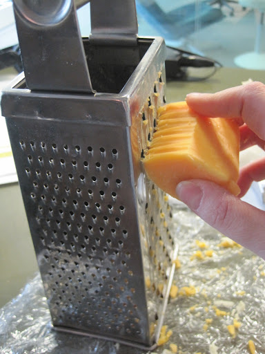 Using the widest holes of a box grater, Monty grates some extra-sharp cheddar.