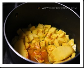Cut mangoes and add red chilly powder, turmeric powder, salt and water