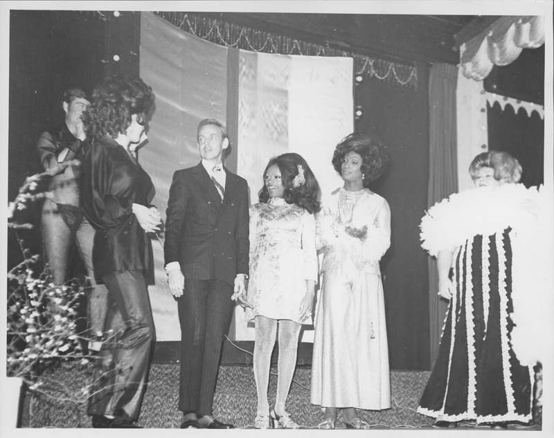 Charles Pierce (in suit) on stage with drag queens at the Mr. Valentine Contest. 1970.