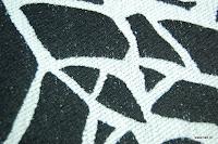 Tkanina obiciowa z efektem metalicznym. Motyw roślinny - liście. Czarno-biała.