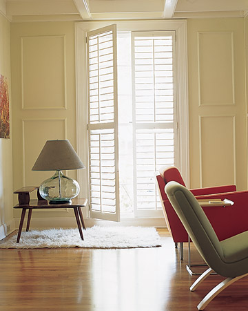 Floor-to-ceiling Plantation shutters add even mimic the wall molding in the room. Plantation shutters have louver blades that are wider than the typical shutter. (Martha Stewart Living)