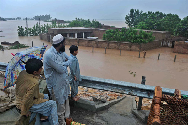 A family in Sindh province, Pakistan watches floodwaters, 12 October 2012. With nearly five million Pakistanis hit by floods that have already claimed some 400 lives, ruined tens of thousands of houses and vast swathes of crops, and left hundreds of thousands living in camps or simply under tarpaulins, the United Nations today appealed for more donations to bolster relief efforts. Abdul Majeed Goraya / IRIN