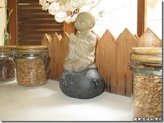 台南Halhali哈拉里咖啡專櫃中正店-餐桌旁可愛的小沙彌雕像。