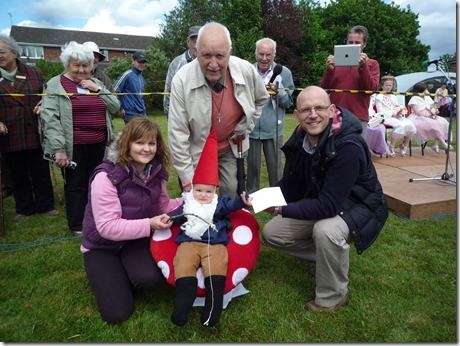 Laurie Clough (standing) presents the prize to fancy dress winner Jack Rhys Chadwick with parents Paul and Hannah Chadwick