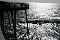 Surfers under the pier at Pismo Beach