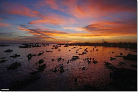 Evacuees displaced from their homes due to fighting between government soldiers and Muslim rebels are seen in boats during sunset at a wharf in Zamboanga city, southern Philippines September 14
