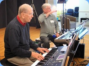 John Beales playing his Korg Pa500 with Gordon Sutherland in the background checking the PA sound level. Photo courtesy of Dennis Lyons.
