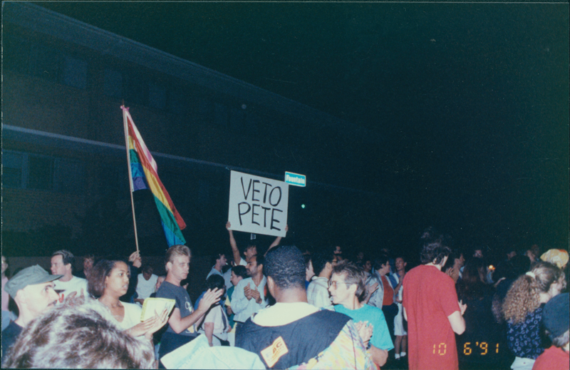 "Protesters at an anti-Pete Wilson march in Silver Lake, one of which is holding a rainbow flag, another a ""Veto Pete"" sign. October 06, 1991."