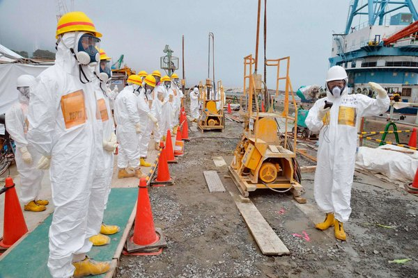Members of a Fukushima panel inspecting the construction of a barrier that is meant to stop radioactive water from leaking into the Pacific ocean. Photo: Kyodo via Reuters