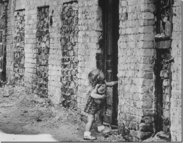 A West Berlin toddler attempts to open a sealed door of a house that has become part of the Berlin Wall in August 1961 via Paul Schutzer - Getty Images