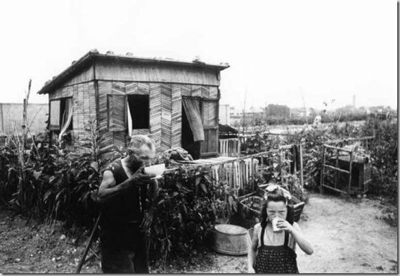 Baracche. Una bambina ed un vecchio bevono all'esterno di una baracca. Milano 1945