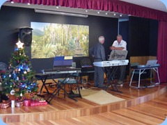 Preparing the stage for the evening's entertainment. Peter Brophy talks with Kevin Johnston. The oil painting in the background had arrived earlier that day for mounting. The painting depicts a scene north of Orewa and was painted by our multi-talented member, John Perkin.