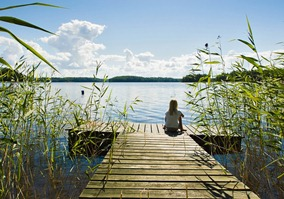 Girl sitting on the pier on a summer day 98472
