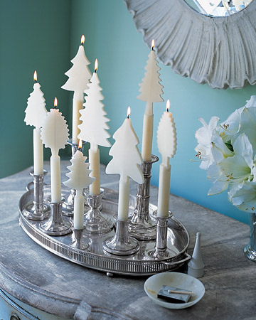Candles adorned with beeswax trees create an enchanting winter landscape on the tabletop.