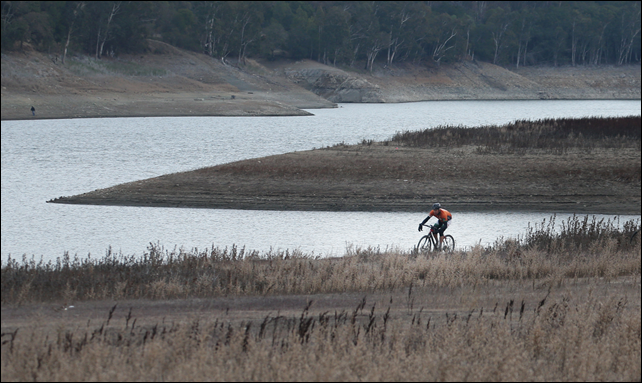 A bicyclist rides in an area that was previously underwater at Lexington Reservoir in Los Gatos Wednesday, 8 January 2014. Photo: Patrick Tehan / San Jose Mercury News