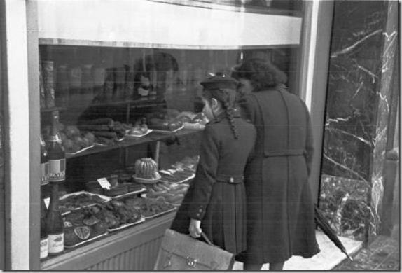 Barcellona - passanti osservano la vetrina di una gastronomia. 1947