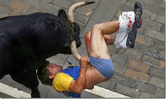 Diego Miralles gets gored by a bull on Estafeta street during the sixth running of the bulls of the San Fermin festival in Pamplona July 12, 2013. The runner, a 31-year-old man from Castellon, Spain, was gored three times. REUTERS/Susana Vera (SPAIN)<br />