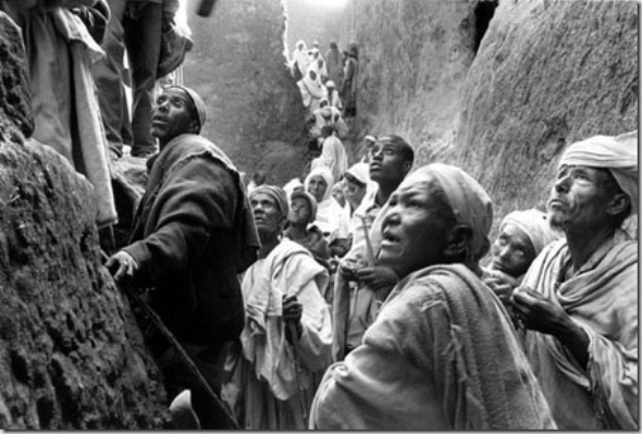 "Pilgrims arriving to Bet Debra Sinai (mount Sinai house) whose interior holds the "" Jesus´cell "", o his tomb. Most of pilgrims are illiterate  farmers of isolated highland areas without exterior communication  whom are shock of Lalibela rock-hewn churches. These magnificent temples, carved from volcanic tufa( the same rock into which the persecuted Christian Troglodytes of Turkey cut their underground cities), defy the imagination. Lalibela performed this feat in order to create a substitute Jerusalem, and to save his people the increasingly difficult and dangerous pilgrimage overseas through hostile territory."