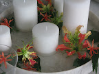 Here, a close-up of the table centerpiece: a low marble vessel filled with water, pillar candles, and flowers.