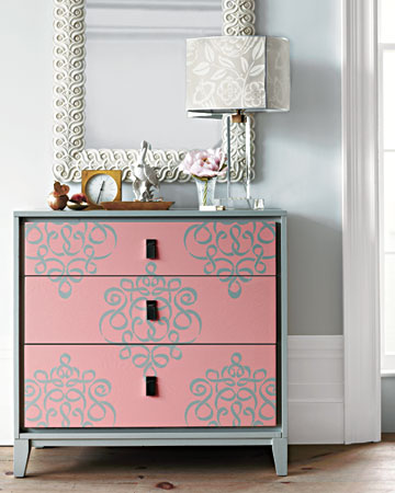 Unexpected pairings often have stunning results. With a stenciled damask pattern, a basic bureau takes a glamorous turn, while a wallpaper-covered shade gives the lamp a bold new glow.