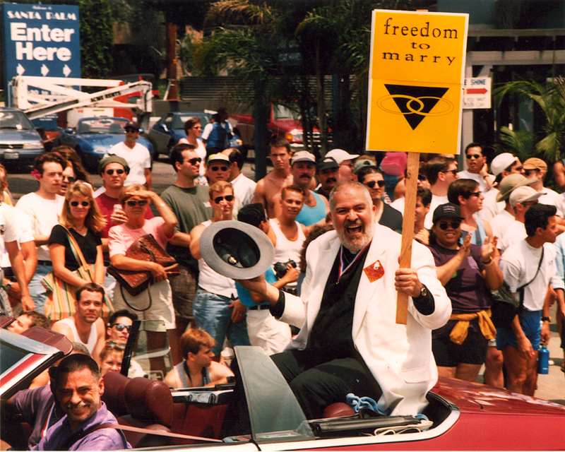 "Reverend Troy Perry carrying a ""freedom to marry"" sign from the back of a car in a Los Angeles Christopher Street West pride parade. Undated."
