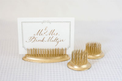 These gold placecard holders would be a perfect tabletop decoration for a dinner party. (100layercake.com)