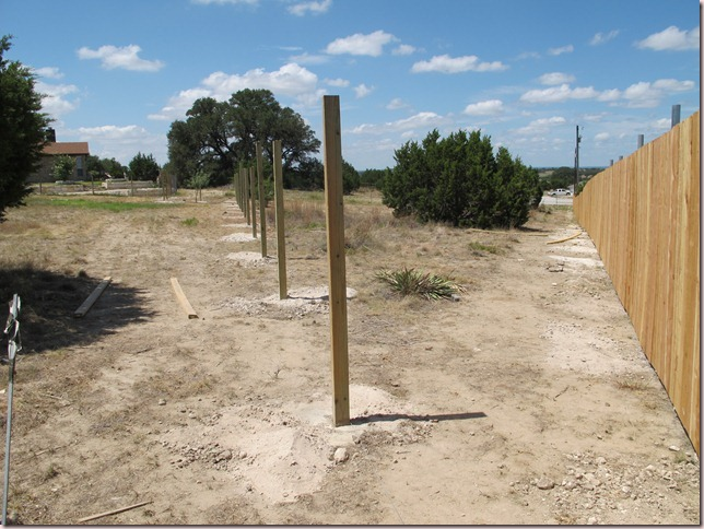 Riding arena to the left of wooden posts, pasture to right