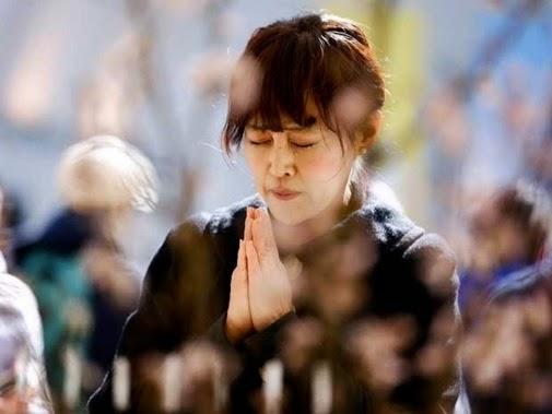 Uma mulher reza em frente a um altar durante evento, em Tóquio