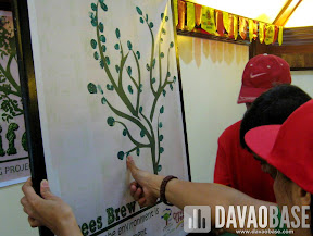 Green thumb prints adorn the Trees Brews Life board