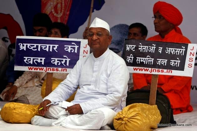 Indian social activist Anna Hazare, 72, center, sits as he begins his fast unto death against corruption, in New Delhi, India, Tuesday, April 5, 2011. Hazare Tuesday began a fast-unto-death demanding enactment of a stronger Lokpal (Ombudsman) Bill through greater involvement of civil society in its drafting. (AP Photo/Mustafa Quraishi)