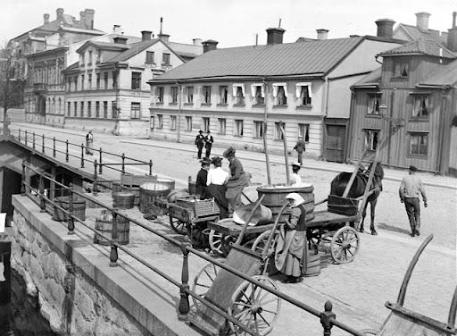 Kvinnor nere vid tvätteriet med baljor och tråg 1900