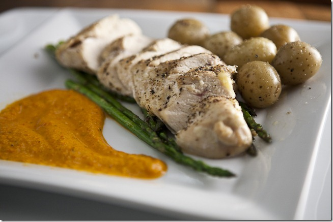 Oven Roasted Seasoned Chicken Breast over Garlic Sauteed Asparagus with Colombian Baby Potatoes and Red Pepper Sauce