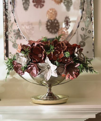 Silk magnolias and lilies are flush with finery: their centers have been replaced with rhinestones, and the petals are coated in red, pink, gold, and silver powder glitters. Real juniper berry branches offer vibrant contrast, and a silver compote provides a fitting base.