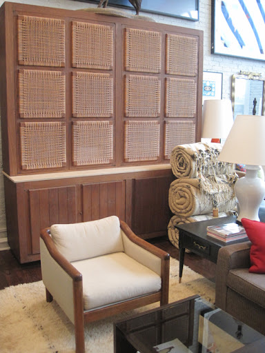 This large 1950s English cerused oak and rattan cabinet in a rustic modern style stands more than 8 feet high. Bottom part has four doors and interior shelves. I love the wicker panels that rest on a slab of travertine.