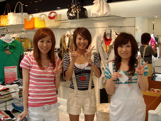 cute Japanese girls in a fashion store in Harajuku making peace signs in Harajuku, Tokyo, Japan